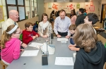 Kyle Smith, principal of Paul Knox Middle School in North Augusta, S.C., left, joins students and SRNS engineer Buford Beavers, center, in a hands-on experiment involving a jar, rubber band, paper clips, and a metal nut. The demonstration of how centrifugal force affects gravitational pull was part of this year's SRS Teach-Ins Program.