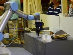 The robot removes the sample from the clear transfer box, out of the two white sample containers, and transports it to the mock-up examination instrument.   Photo courtesy of Idaho National Lab.