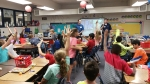SRR Engineers Austin Chandler (left) and Jeff Iaukea (right) use interactive games to make science fun for fourth graders at Hammond Hill Elementary.