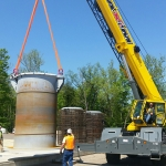 Workers place a vertical storage cask liner on a construction pad.