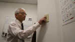 Photo of a man switching on or off a light switch on a wall.