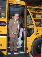 Ed McNeel, superintendent of Corbin's school district, poses aboard the district's new hybrid-diesel bus.   Photo Courtesy of Susie Hart.