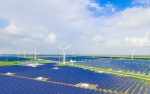 Photo of a field of solar panels and windmills.