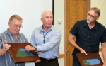 At Tuesday's Grand County Council meeting in Utah, Moab Federal Project Director Donald Metzler, center, moves a piece from a plaque representing Moab's uranium mill tailings pile to a plaque representing the disposal cell in recognition of the site achieving a milestone by shipping 6 million tons of the tailings. Grand County Council Chair Gene Ciarus is on the left and Grand County Council Vice Chair Lynn Jackson is on the right.
