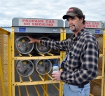 Mike Tidwell performs a leak check and inspection on propane tanks