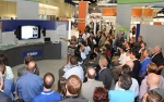 Photo of a crowd of people watching a presentation.