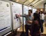Ian Baughman (left), University of Michigan, discusses his research to optimize the signatures of uranium in laser ablation spec