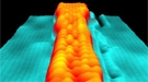 """Scanning tunneling microscopy image shows a variable-width graphene nanoribbon. Atoms are visible as individual """"bumps."""""""