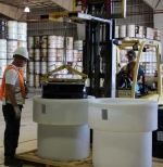 A product drum of mixed low-level waste is lowered into a high-density polyethylene macro-pack.