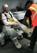 Members of the Hanford site team observe Advanced Mixed Waste Treatment Project workers at the Idaho site putting on protective equipment. The Level B protective suit is custom-designed to provide maximum flexibility and protection against potential workplace hazards. The containment suit, coupled with the breathing equipment shown in the photo below, enables work to be conducted safely in high-hazard atmospheres.