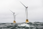 Photo of two offshore wind turbines in the ocean.