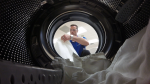 Photo from the perspective of the inside of a washing machine, showing the door open and a man with laundry beyond.
