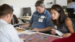 Ted Wright of the Stillaguamish Tribe and Shannon Loeve of Turtle Mountain Band of Chippewa review resource maps during a 2014 tribal energy project development and financing workshop in Golden, Colorado. Photo by Amy Glickson, NREL 31795.