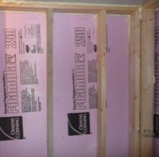 This photo shows a framed basement wall with insulation in between the studs.