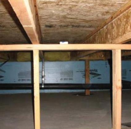 This photo shows the interior of a framed crawlspace with insulation installed.