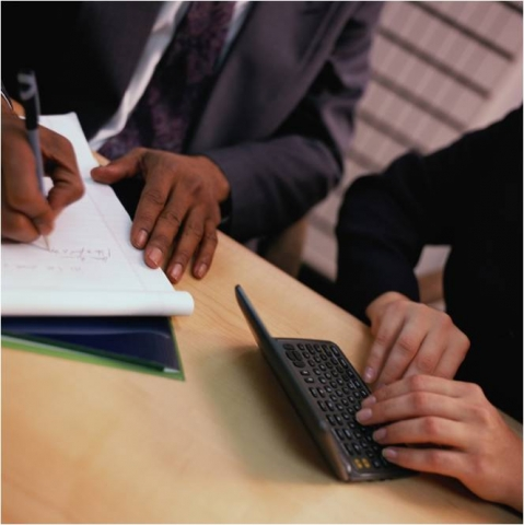 Photo of two people sitting at a table; their bodies are only partially seen as they rest their hands on the table, presumably conducting a meeting. The one on the left, a man, has a pad of paper and pen, while the person on the right, a woman, is punching keys on a handheld electronic device.