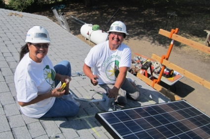 Photo of two tribal members installing a rooftop solar panel.