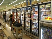 Photo of a row of freezer cases at a supermarket with a ladder and workcart nearby and a maintenance worker standing next to them.