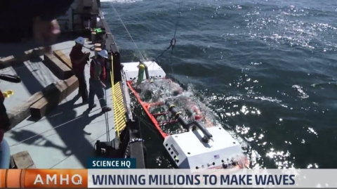 A screenshot of a news item showing a team of scientists lowering a large piece of machinery into the open ocean.