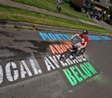 A photo of a bicyclist riding along a paved surface with painted lettering on it.