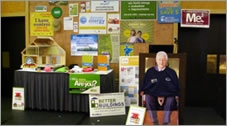 Photo of an event exhibit, with a man sitting next to it.