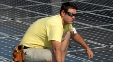 Photo of a young man working on solar panels.