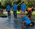 A photo of several boys in matching T-shirts dancing on a paved surface.