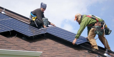 Image of people installing a solar panel on a roof.