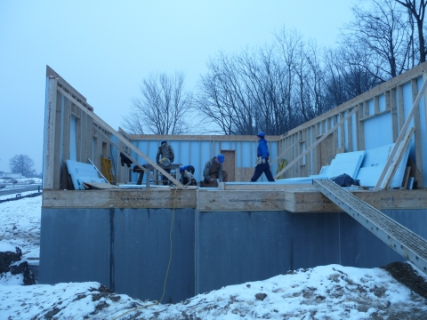 Photo of workers installing an extended plate and beam wall system