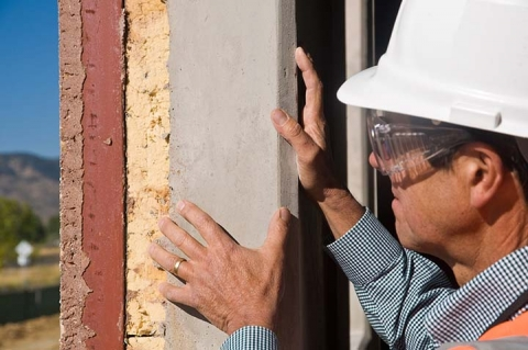 Man with a white hard hat examines panels installed on the exterior wall of a building under construction.
