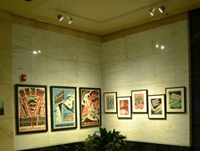 Photo of a corporate lobby with LED track lights illuminating eight framed pieces of art.