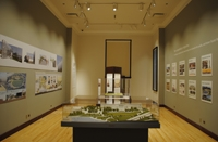 Photo of a museum gallery with a display case at center and LED track lighting overhead.
