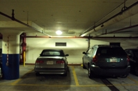 Photo of cars in a parking garage with an LED fixture on the ceiling above.