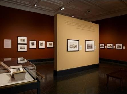 Photo of museum exhibit with pictures hanging on walls and illuminated by track lights.