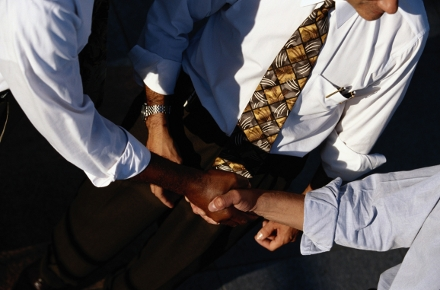Photo of three men in business attire with ties, of various ethnicities, shaking hands. Their faces are not visible, just their torsos as their hands meet.