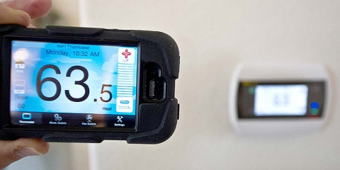 Image of a phone with a thermostat app with a thermostat on the wall in the background.