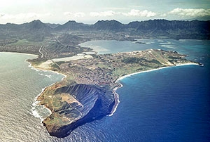 Photo of the HINMREC Kaneohe Bay site.   Shows a hilly peninsula jutting out into the ocean.