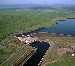 Photo of a hydropower plant located on a river with grassy hills around it.