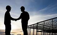 This photo shows two men silhouetted against a sky shaking hands, with the frame of a building under construction in the background.