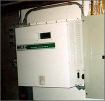A photo of an inverter, which is basically a small, beige metal box with a display window on the front and vents on the side.