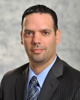 Photo of man with short-cropped black hair wearing gray pin-striped suite, blue shirt and tie.