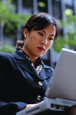 A photo of a young Asian female working on her laptop in an outdoor setting, near an office building.