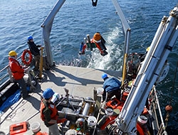 Photo of several men on a floating platform that is lowering monitoring tools into the ocean.