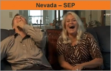 Photo of a man and woman sitting on a couch next to each other, facing the camera and laughing uproariously.