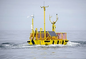 Photo of the NNMREC OceanSentinel, showing a the floating, metal test unit floating in the ocean.