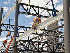 Photo of NREL's Research Support Facility under construction, with two workers straddling I-beams.