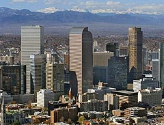 Photo of the Denver skyline with Wells Fargo Center building in the center of the image and the Rocky Mountains in the background.