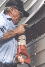 Photo of worker cutting into the siding of a house with a reciprocating saw.