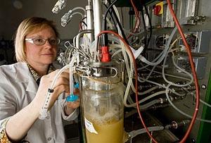 Photo of a woman in goggles handling a machine filled with biofuels.