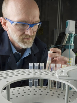 Photo of a man in goggles looking at test tubes full of biodiesel.